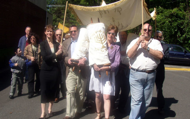 Neve Shalom congregants parade with members of Congregation Adath Israel in Woodbridge as they carry Torah scrolls from the Woodbridge synagogue before placing them in their new home in Metuchen, as the two synagogues merged on May 21, 2006. Photo by De