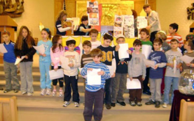 Students at the Solomon Schechter Day School of Raritan Valley in East Brunswick affix photos and words to a hanukkia during the Terrific Thursday program, which raised close to $500 for the Jewish Federation of Greater Middlesex County. Photos