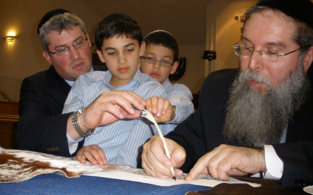 Seth Cohen, left, and his sons, Lev, 10, and Gabriel, eight, help inscribe the first letters of a Torah scroll being written in memory of their wife and mother by the Young Israel of East Brunswick. Guiding them is scribe Zvi Chaim Pincus. Photos by Debra