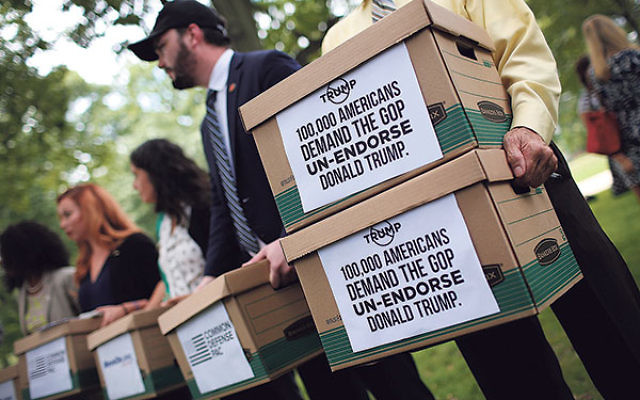 Former members of the U.S. military carrying boxes with more than 100,000 signatures requesting that Sen. John McCain and other Republican leaders withdraw their endorsement of Republican presidential candidate Donald Trump following a press conference in