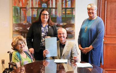 Babs Siperstein, left, watches as Gov. Phil Murphy signs the law simplifying the procedure to change gender identity on birth certificates. Looking on are Jennifer Long, standing, left, and Sue Fulton. (Photo courtesy of Office of Gov. Phil Murphy)
