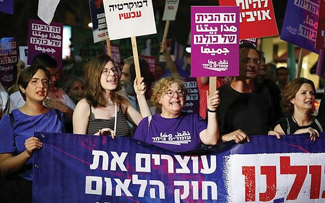 """A protest against the """"Jewish Nation-State Bill"""" in Tel Aviv on July 14. The pink sign reads in Arabic and Hebrew, """"This is the home of all of us."""" (Jack Guez/ AFP/Getty Images)"""