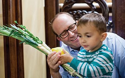 Rabbi Philip Bazeley of Anshe Emeth Memorial Temple explains the significance of the etrog and lulav to a young congregant. Photo by Ouriel Morgansztern