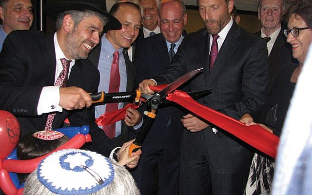 Rabbi Mendel Solomon cuts the ribbon held by Livingston Council Member Michael M. Silverman, second from right, and others. Photo by Johanna Ginsberg