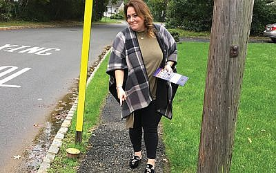 Livingston Town Council candidate Debbie Burack points to one of the many damaged sidewalks she hears residents complain about. Photos by Johanna Ginsberg