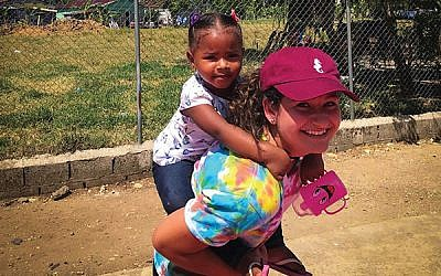 Alina Keller gives a piggyback ride to a Dominican child. Photos courtesy Alina Keller