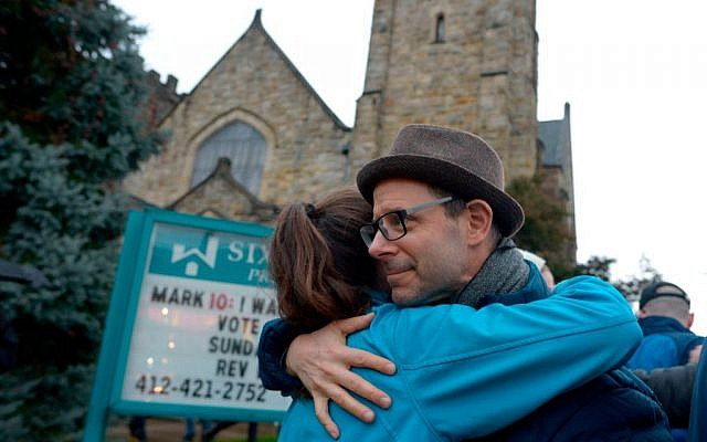 Matthew Chinman, 49, of Squirrel Hill, hugs a fellow community member during a vigil held to remember those who died earlier in the day during a shooting at the Tree of Life Synagogue in the Squirrel Hill neighborhood of Pittsburgh on October 27, 2018. - The gunman who killed 11 people at a synagogue in Pittsburgh will face federal charges that carry the death penalty, the US Justice Department said. (Photo by Dustin Franz / AFP)        (Photo credit should read DUSTIN FRANZ/AFP/Getty Images)