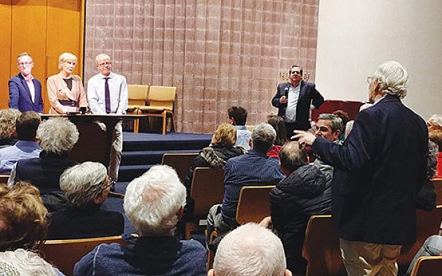 An audience member puts a question to the media panel at Temple B'nai Abraham, as Rabbi Cliff Kulwin watches.