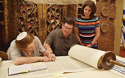 Scott Borsack lays his hand on the hand of soferet Linda Coppleson as she inscribes words as part of her repair work on the Torah scroll at the Jewish Center; his wife, Charlene, awaits her turn. Photo by Talya Feldman