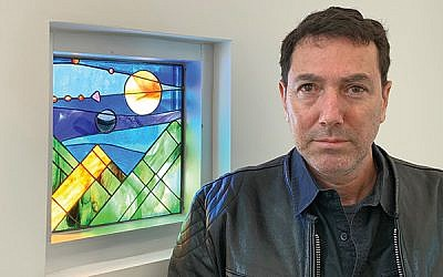 Designer Lev Gal Wertman stands beside the window depicting the creation of the sun, moon, and stars at Gottesman RTW Academy. Photos by Johanna Ginsberg