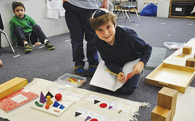 A third grader works with grammar symbols and shapes to learn language construction. Photo courtesy Netivot