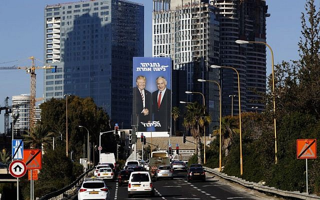 """A picture taken on February 3, 2019 in the Israeli coastal city of Tel Aviv shows a giant election billboard of Israeli Prime Minister Benjamin Netanyahu and US President Donald Trump shaking hands. The writing on the billboard reads in Hebrew """"Netanyahu, in another league"""". Getty Images"""