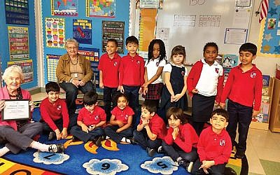 Kindergarten students at Cedar Hill Preparatory School are joined by Maxine Prescott, seated, left, and Muriel Hyman. Prescott holds a certificate stating that Stein Assisted Living's Always a Teacher program received honorable mention for innovation from Leading Age, the state nonprofit for senior organizations. Photos by Debra Rubin
