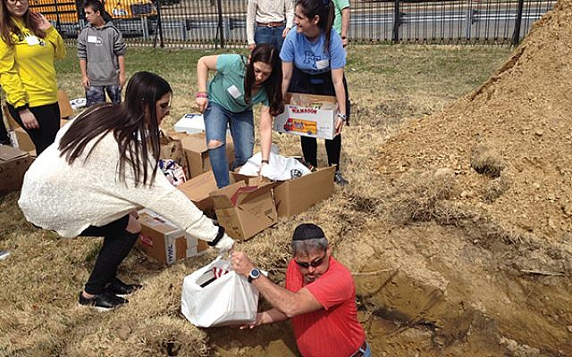 With the assistance of Congregation Beth Ohr, teens aid in the burial of sacred books at Beth Israel Mordechai Cemetery in Parlin.