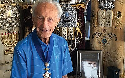 Ed Mosberg, wearing his Polish Order of Merit with a part of his collection of Holocaust memorabilia.