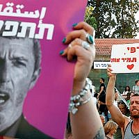 "Members of the LGBT community hold a banner reading in Hebrew ""a homophobic racist has to quit"" during a July 14 rally in Tel Aviv against Israel's Education Minister Rafi Peretz (portrait) following his remarks on gay conversion therapy. JACK GUEZ/AFP/Getty Images"