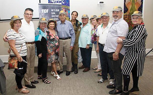 Attendees of the FIDF fund-raiser at Chabad House of Monroe included, from left, Hanna Gelman, Len Posnock, Frieda Posnock, Julie Tajfel, Henry Tajfel, Sgt. Maya, Avi Rozencwaig, Annette Rozencwaig, Rachel Bornstein, Itzik Feifowitz, Arie Sharon, and Haya Sharon.  Photo courtesy Chabad House of Monroe