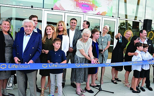 Paula Gottesman, at center, cuts the ribbon at the grand opening of LifeTown: The Jerry Gottesman Center, named for her husband who was an early backer of the project.  Photo by Jerry Siskind