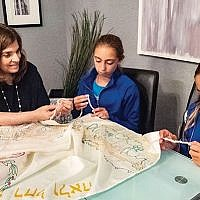 Rabbi Lois Ruderman in a congregant's home with students looking at tzitzit like the ones they will tie for tallitot of their own.  Photo by Carol Dickert