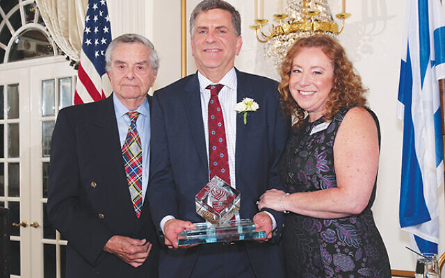 Jeffrey Landau, center, executive vice president and chief lending officer of the Bank of New York Mellon, receives the Commerce and Industry Division's Shimon Peres Leadership Award. He is flanked by father Morton, and wife Michele Landau. Photos by Robert Schneider