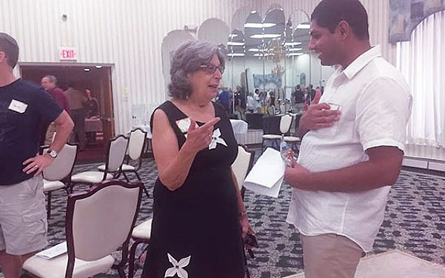 Susan Uram Levinson, a cochair of the Community Café program, chats with panelist Suleman Amoon, a Christian refugee from Pakistan. Photos by Debra Rubin