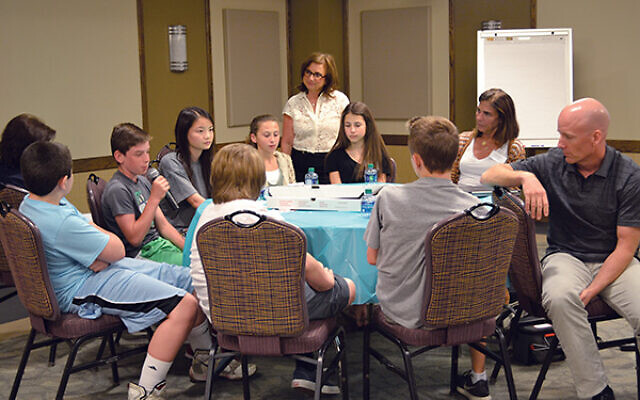 "Dale Daniels, standing, watches as students from Cedar Drive Middle School in Colts Neck take part in ""Lunch with a Survivor"" in 2016. Photos courtesy Chhange"