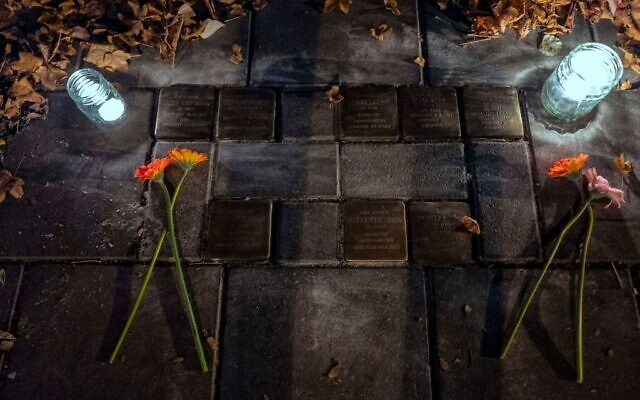 "Flowers and lit candles are placed next to ""Stolpersteine"" commemorating Holocaust victims, in Berlin, on November 10, 2018, one day after the 80th anniversary of the Kristallnacht Nazi pogrom. Getty Images"