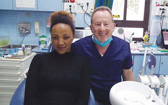 Dr. Neal Gittleman of Pennington with a patient in the Trudi Birger Dental Clinic in Jerusalem.