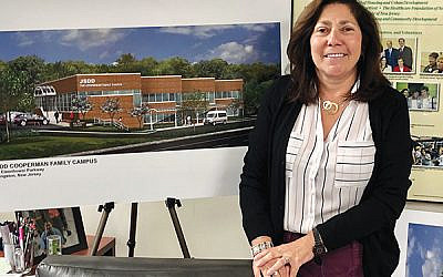 JSDD executive director Linda Press with a rendering of the JSDD Cooperman Family Campus. Photo by Jed Weisberger