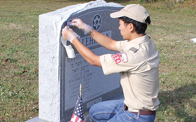 Evan Kuo places a sticker on a headstone at Monmouth Fields Jewish Cemetery, marking it as belonging to a war veteran.  Photo courtesy Evan Kuo