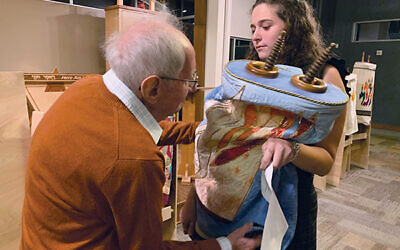 Emerson Lederman hands a rescued Torah scroll from Temple Sinai to Peter Fleischmann during a ceremony at Temple Sholom in Scotch Plains. Photos by Johanna Ginsberg