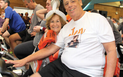 """Sandy Goodman, at left, wears a boxing robe and gloves at each Cycle for Survival event to show she's """"fighting"""" for a cure. Her husband, Len, is at right. Photos courtesy Sandy Goodman"""