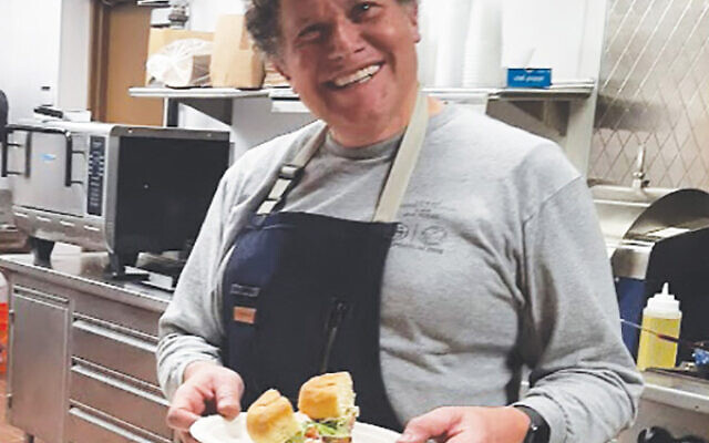 "College Avenue café mashgiach David Weintraub of Highland Park shows off a Beyond Burger prepared with tomato, lettuce, pickled onion, and ""magic sauce."" Photo by Debra Rubin"