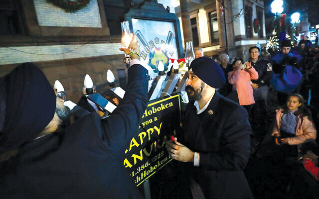 Attorney General Gurbir Grewal, at left, helps light the candle for the first night of Chanukah on Dec. 22. Photo Courtesy NJ Office of the Attorney General