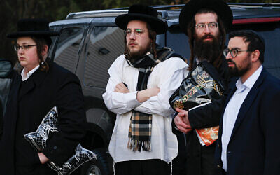 Chasidic community members gather outside the home of Rabbi Chaim Rottenberg in Monsey, N.Y.  Kena Betancur/AFP via Getty Images