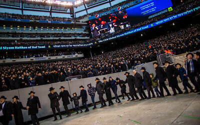 EAST RUTHERFORD, NJ - JANUARY 01: Orthodox Jews sing and dance during the 13th Siyum HaShas, a celebration marking the completion of the Daf Yomi, at the MetLife Stadium on January 1, 2020 in East Rutherford, New Jersey. Security was tightened at the event, where the Talmud is read in its entirety, after a rise in anti-Semitic incidents in the area. (Photo by Eduardo Munoz Alvarez/Getty Images)
