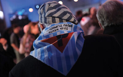 Shoah survivors at the official ceremony marking the 75th anniversary of the liberation of Auschwitz were given scarfs reminiscent of their prison uniforms. Sean Gallup/Getty Images