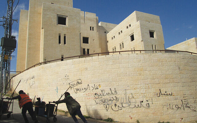 The large stone building in Abu Dis that — according to the never-adopted Beilin-Abu Mazen peace plan of the 1950s — was supposed to be used as the Palestinian parliament is empty, its walls covered in graffiti. Photos by Michele Chabin