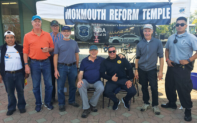 Dean Ross, who founded Shine-A-Light, seated, left, with Red Bank Police Officer Lt. Juan Sardo, surrounded by volunteers, including members of Monmouth Reform Temple and the Red Bank Policemen's Benevolent Association. Photo courtesy Dean Ross