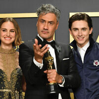 Oscar winner of Adapted Screenplay Taika Waititi, center, with presenters Natalie Portman and Timothée Chalamet. Amy Sussman/Getty Images