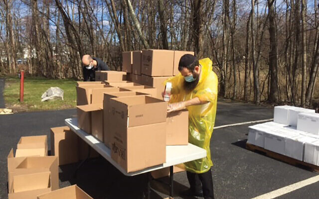 A volunteer tapes up cardboard boxes to be filled with kosher for Passover foods. Photo Courtesy JRA