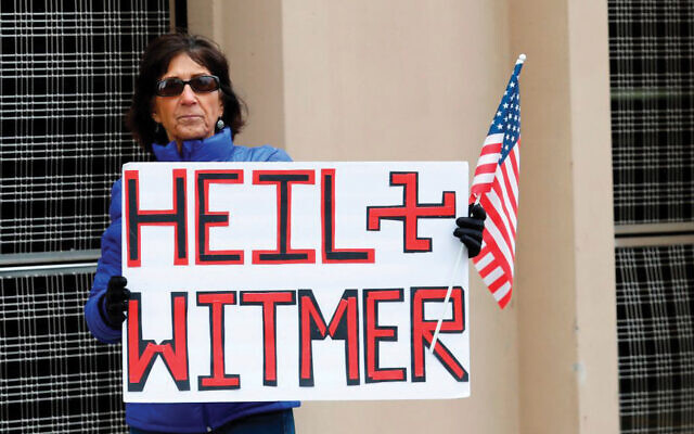 A protestor last week in Lansing, Mich., who compared Gov. Gretchen Whitmer to a Nazi for extending the state's lockdown orders. JEFF KOWALSKY/AFP via Getty Images