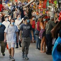 Shoppers wearing protective masks against the novel coronavirus, walk through the Shuk HaCarmel on May 7, 2020. JACK GUEZ/AFP via Getty Images