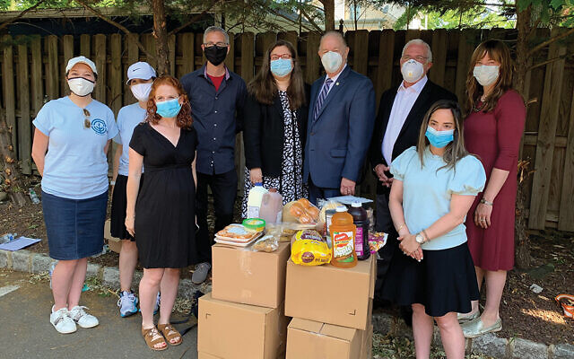 Those at last week's kosher food pickup include, back row, from left, Rebecca Hindin, Mandi Perlmutter, Steve Karp, Assemblywoman Annette Quijano, Elizabeth Mayor J. Christian Bollwage, Assemblyman Gary Schaer, and Yael Bleicher. In front is staff from Teach NJ, including Katie Katz, at left, and Renee Klyman. Photos by Johanna Ginsberg