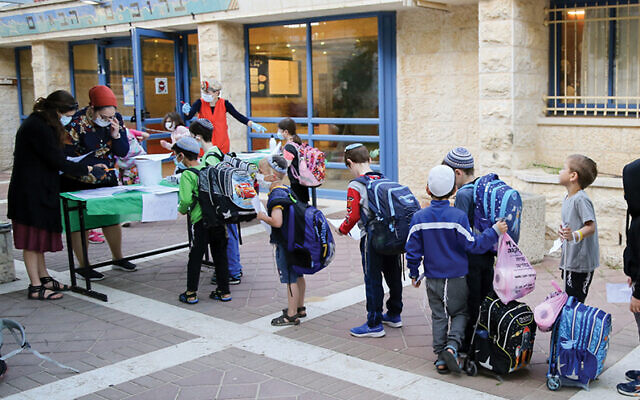 Israeli students at the Orot Etzion school in Efrat wear protective face masks as they return to school in early May. Gershon Elinon/Flash90