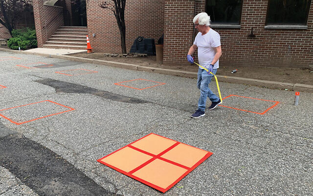 Mike Cumberton painting boxes in the parking lot at Synagogue of the Suburban Torah Center in Livingston. Each box will serve as a member's personal space when services resume outdoors on June 4. Photo by Johanna Ginsberg