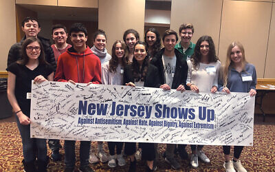 Leaders for Tomorrow (LFT) students in 2019 with a banner during AJC's #ShowUpForShabbat weekend commemorating the first anniversary of the mass shooting at the Tree of Life synagogue in Pittsburgh. Courtesy AJC New Jersey