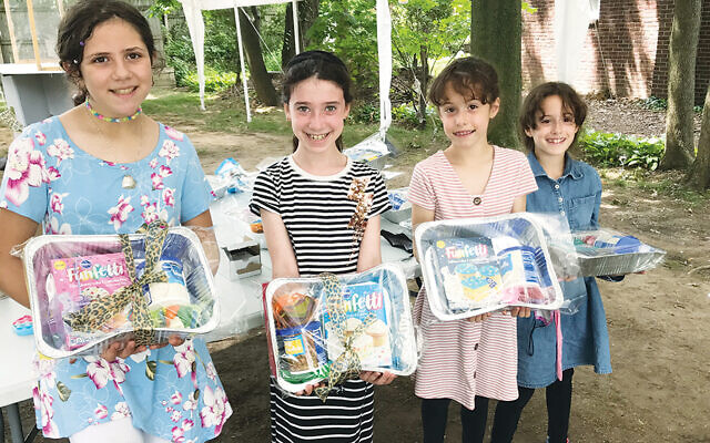 Temima Baker, Orit Strassman, Belana Dworkis, and Danielle Dworkis hold the birthday kits they packed and will donate to a local food pantry.