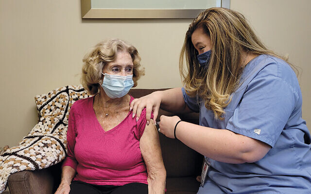 Nancy Rivera, right, a JFSCNJ registered nurse, vaccinates a Union County resident. (Courtesy JFSCNJ)