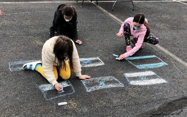 Students and community members  greeted students returning to Temple Sholom for in-person, parking lot classes last April, where the ground made for a convenient blackboard.